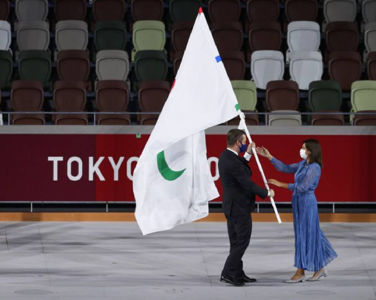 Andrew Parsons (L), president of the International Paralympic Committee (IPC), passes the Paralympic flag to Anne Hidalgo, mayor of Paris, during the closing ceremony of the Tokyo 2020 Paralympic Games at the Olympic Stadium in Tokyo, Japan, Sept. 5, 2021.