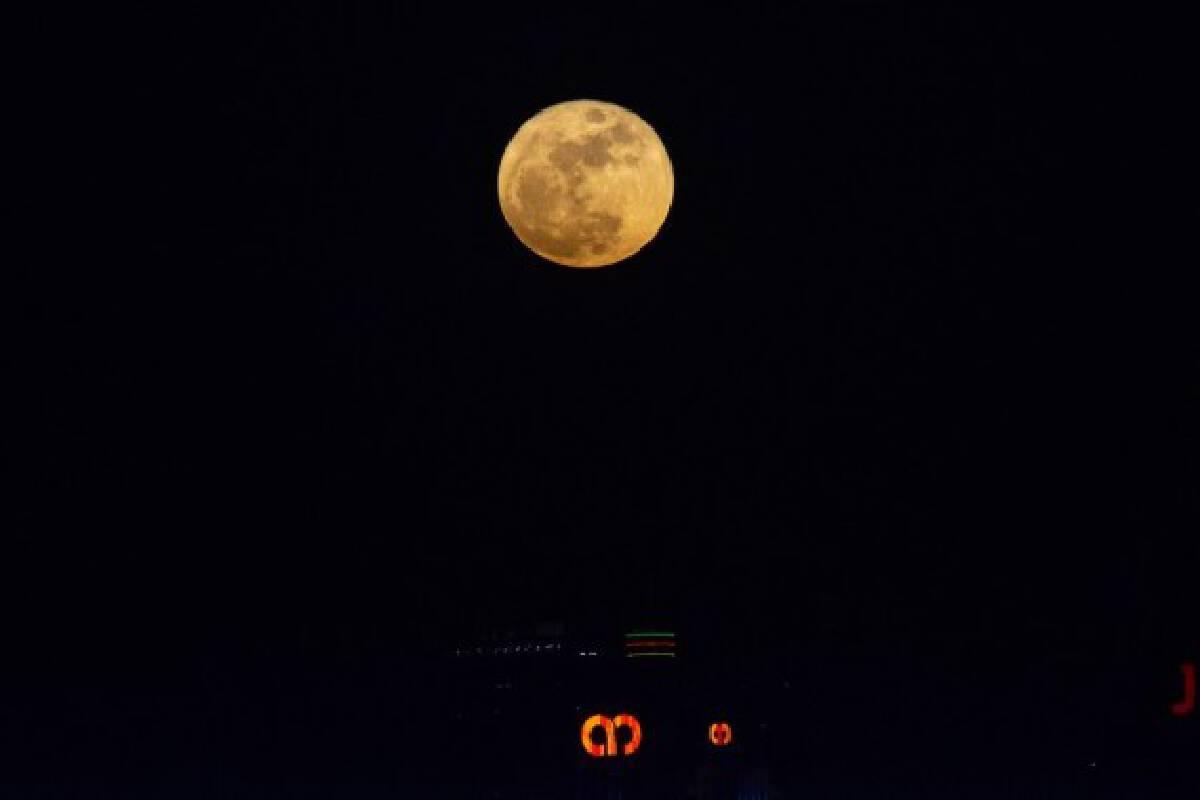 A full moon is seen against the skyline of Kuala Lumpur, Malaysia, on the occasion of Mid-Autumn Festival on Sept. 21, 2021. (Photo by Chong Voon Chung/Xinhua)