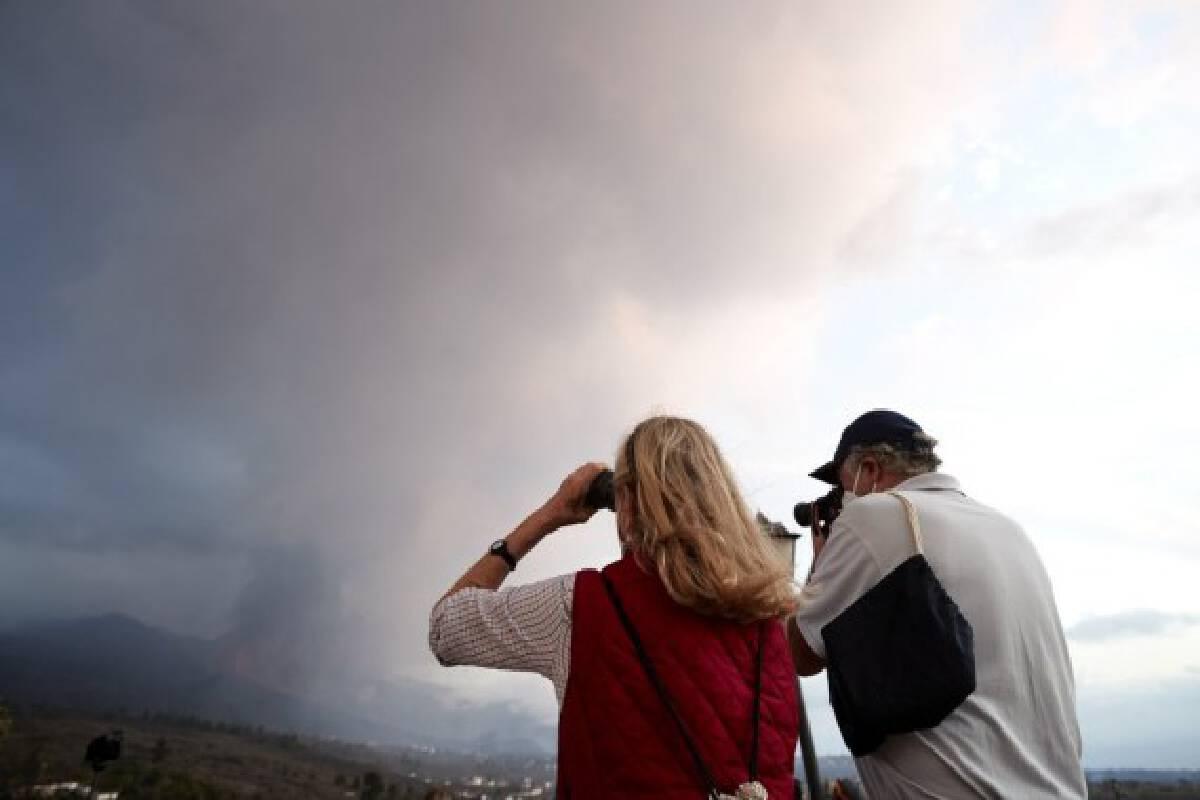 People watch the scene of volcanic eruption of Cumbre Vieja volcano in La Palma, Spain, Sept. 23, 2021.(Xinhua/Meng Dingbo)