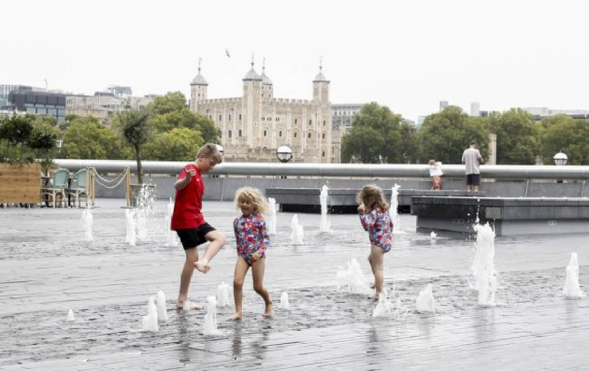 Children play with water in a fountain near Tower of London in London, Britain, on Aug. 13, 2021.