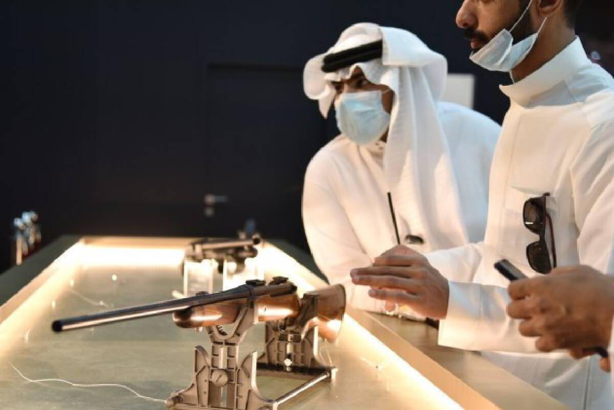 Visitors look at guns during the Saudi International Falcons and Hunting Exhibition at the headquarters of the Saudi Falcon Club in Mulham, north of Riyadh, Saudi Arabia, on Oct. 5, 2021. (Xinhua/Wang Haizhou)