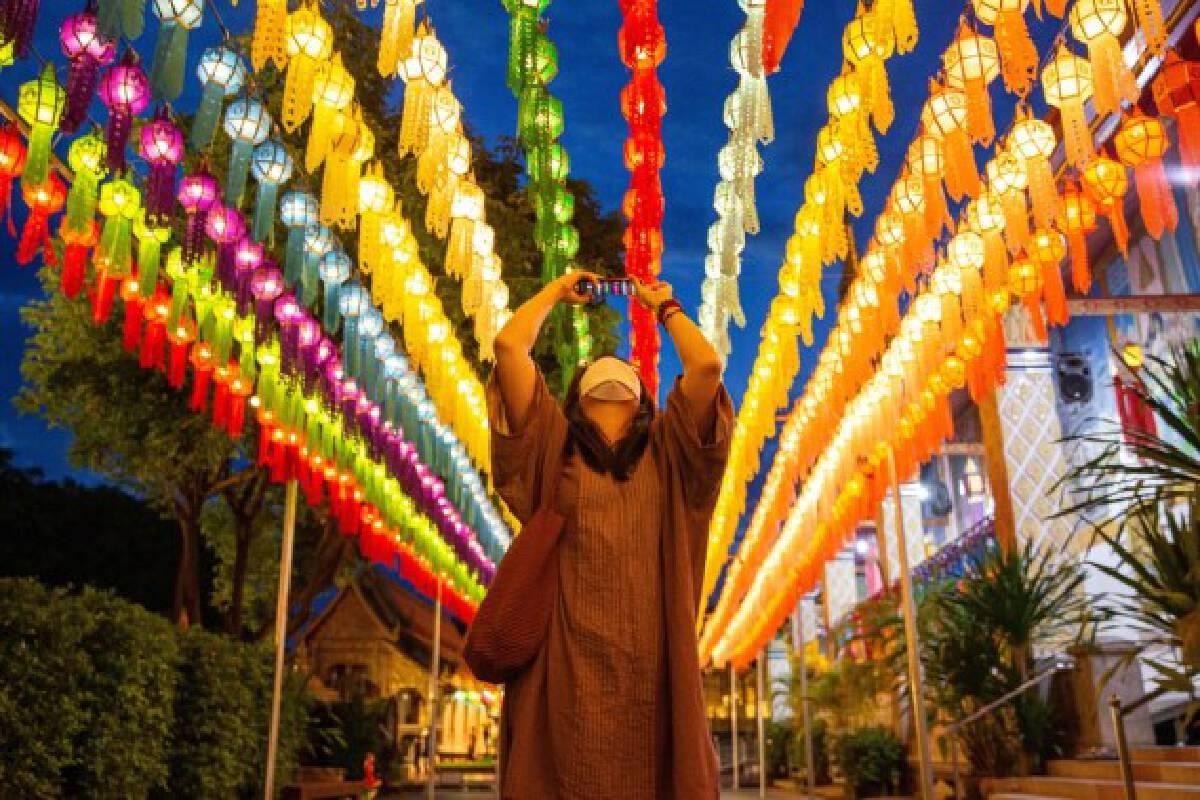 A tourist takes photos of lanterns at the Wat Phra That Hariphunchai in Lamphun, Thailand, Oct. 25, 2021. (Xinhua/Wang Teng)